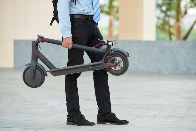 Homme avec scooter debout à l'extérieur