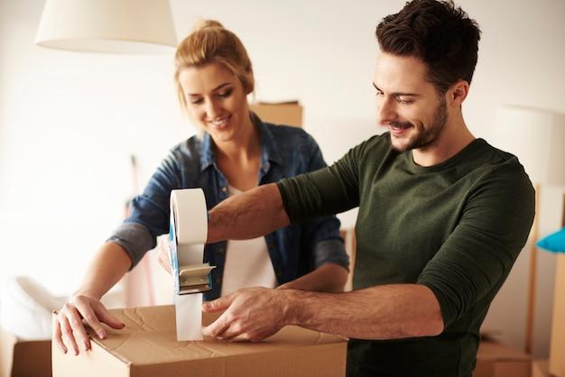 Homme scotchant une boîte en carton pour se déplacer