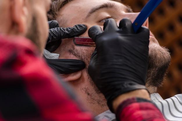 Homme se barbe avec une lame