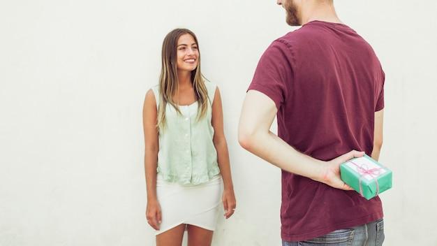 Un homme se cache derrière son dos pour sa petite amie