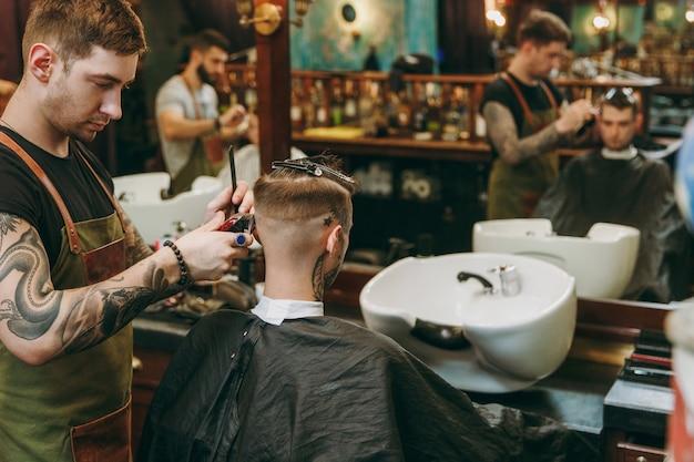 Homme se coupe de cheveux à la mode au salon de coiffure. le coiffeur masculin en tatouages au service du client.
