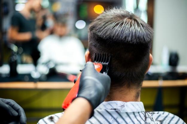 Homme se coupe les cheveux avec reflet de miroir flou