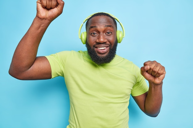 L'homme se déplace au rythme de la musique porte des écouteurs sans fil sur les oreilles vêtus d'un t-shirt vert s'amuse