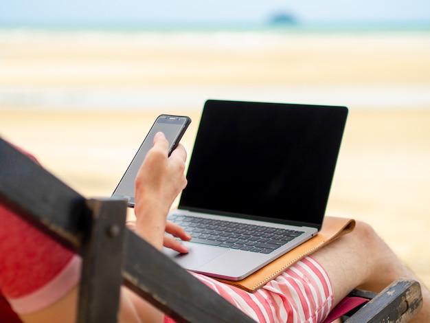 L'homme se détend sur le lit de camp et travaille en ligne.