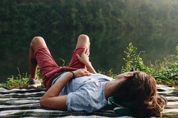 Homme se détendre au bord d'un lac dans la forêt