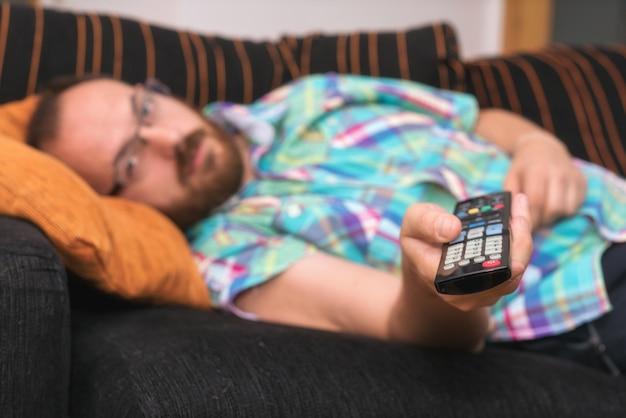 Homme se détendre dans un canapé avec télécommande en regardant la télévision.