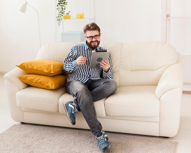 Homme se détendre à la maison sur un canapé avec tablette