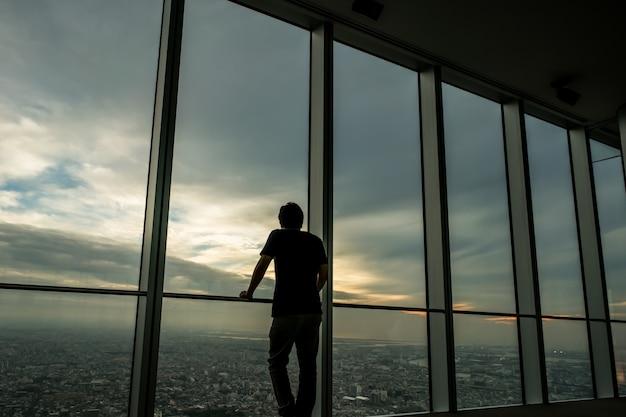 Homme se détendre et profiter de la vue depuis la fenêtre