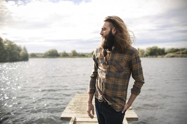 Homme se détendre en se promenant au bord du lac