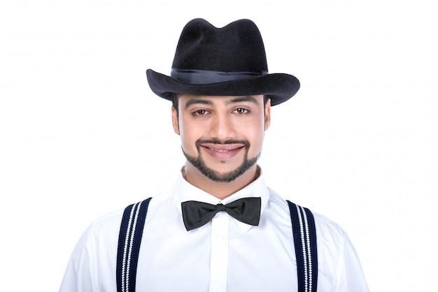 Un homme se dresse dans un chapeau et sourit