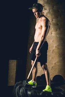 L'homme se dresse avec un pneu de roue hammer sledge crossfit training