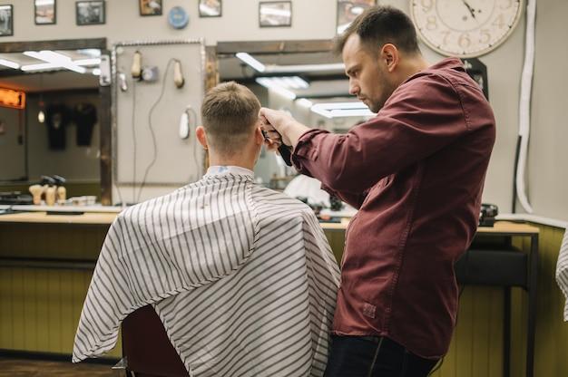 Homme se faire couper les cheveux dans un salon de coiffure