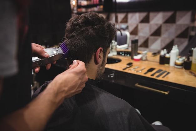 L'homme se fait couper les cheveux avec une tondeuse