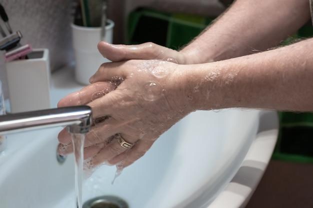 L'homme se lave les mains avec du savon liquide au-dessus d'un évier à la maison en gros plan