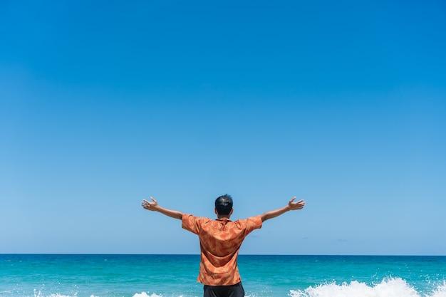 L'homme se lève les mains jusqu'au concept de liberté de ciel avec un ciel bleu.