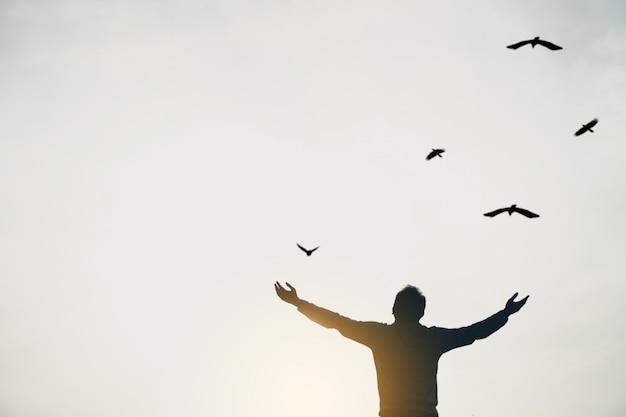 L'homme se lève les mains vers le ciel en regardant les oiseaux voler à travers le concept de liberté de métaphore avec le coucher du soleil ciel ton noir et blanc.