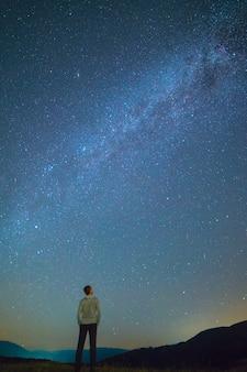 L'homme se lève et regarde le ciel étoilé. la nuit