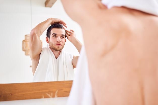Homme se peignant les cheveux en se tenant debout avec une serviette blanche sur le cou près du miroir dans la salle de bain