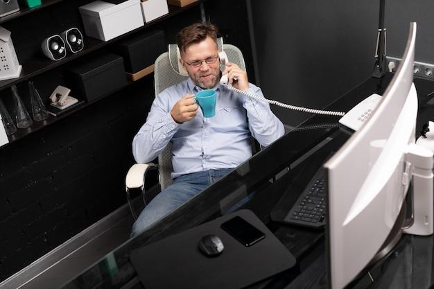 L'homme se pencha en arrière sur sa chaise, buvant du café et parlant sur un téléphone fixe