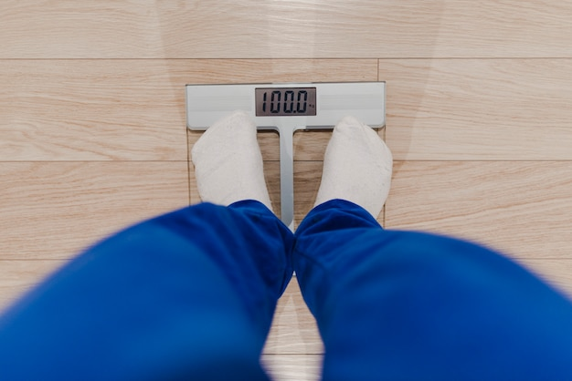 Homme se pesant sur une balance numérique. problème de surpoids. concept de régime.