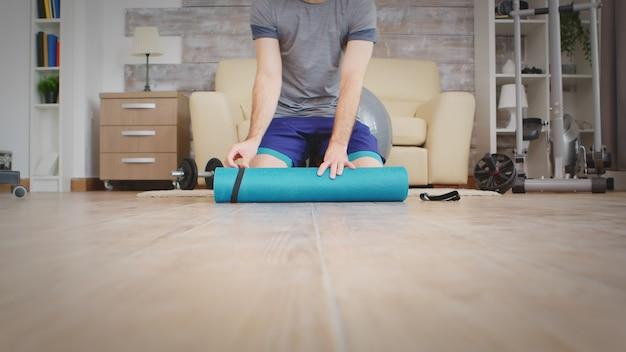 Homme se préparant au yoga dans un salon confortable.