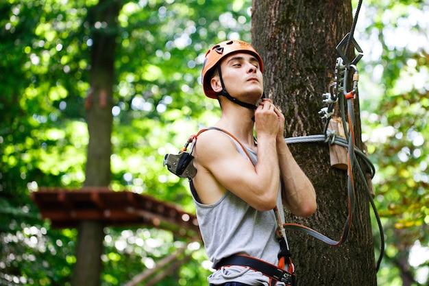 L'homme se prépare à grimper sur les cordes dans le parc