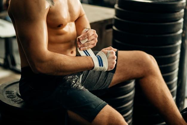 Homme se prépare pour la formation, en enveloppant ses mains avec du ruban adhésif