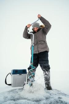 L'homme se prépare pour la pêche dans le lac gelé
