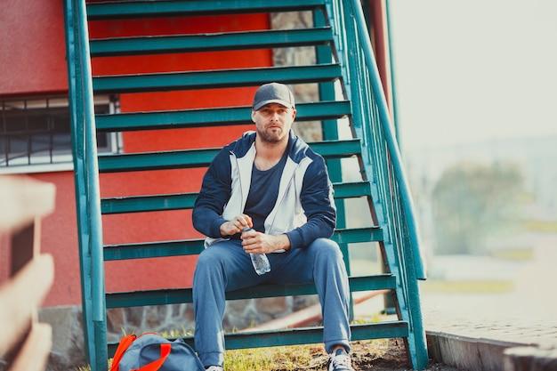 L'homme se prépare à s'entraîner assis sur le banc dans le parc
