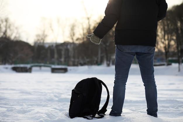 Un homme se promène dans la ville un jour d'hiver enneigé.
