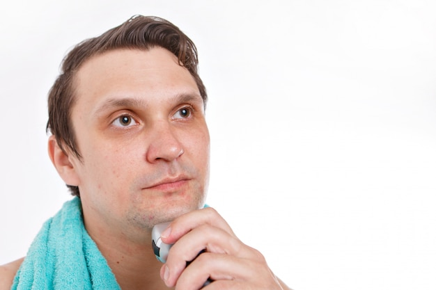 L'homme se rase le chaume. mec nettoie sa barbe avec un rasoir électrique. soins du matin dans la salle de bain.