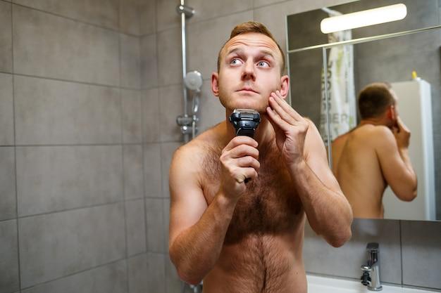 Un homme se rase le visage avec un rasoir électrique devant un miroir. irritation de la peau. procédure de bain