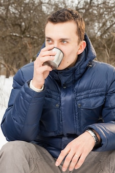 Homme se réchauffant avec du thé chaud