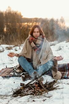 L'homme se réchauffe à côté d'un feu de camp en hiver