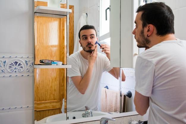 Homme se regardant dans un miroir dans la salle de bain. il se rase la barbe