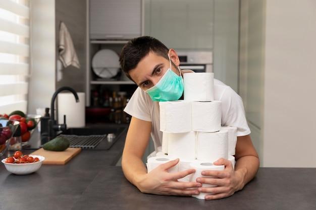 Un homme se réjouit du papier hygiénique, à cause de la panique et des carences causées par l'épidémie du virus covid19.