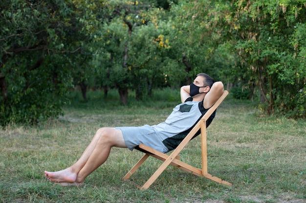 Homme se reposant sur une chaise longue dans un masque médical protecteur sur son visage bronzer à l'extérieur de la pelouse verte dans le jardin guy sur un transat le week-end d'été