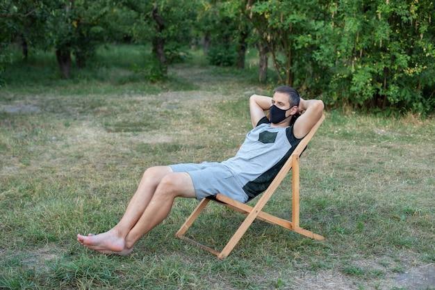 Homme se reposant sur une chaise longue dans un masque médical protecteur sur son visage en train de bronzer à l'extérieur de la pelouse verte dans le parc