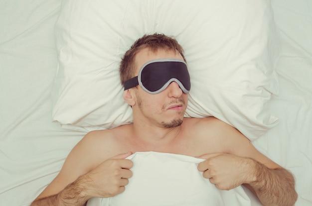 Homme se reposant dans un masque pour dormir. chaume sur son visage. homme fatigué