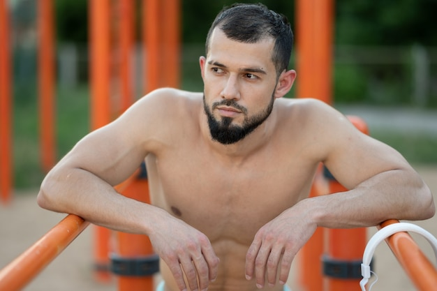 Un homme se repose après avoir fait du push ups sur les barres à l'extérieur pendant la journée