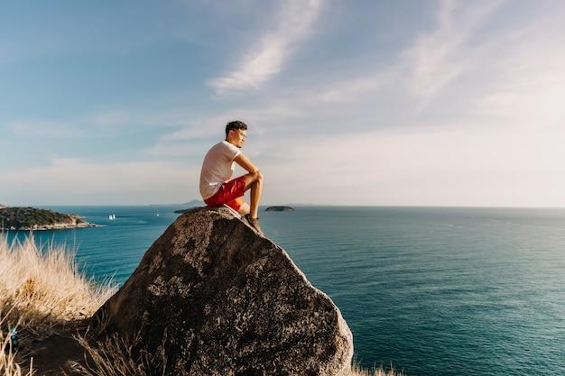 L'homme se repose sur le rocher de la falaise après avoir terminé son sentier de randonnée