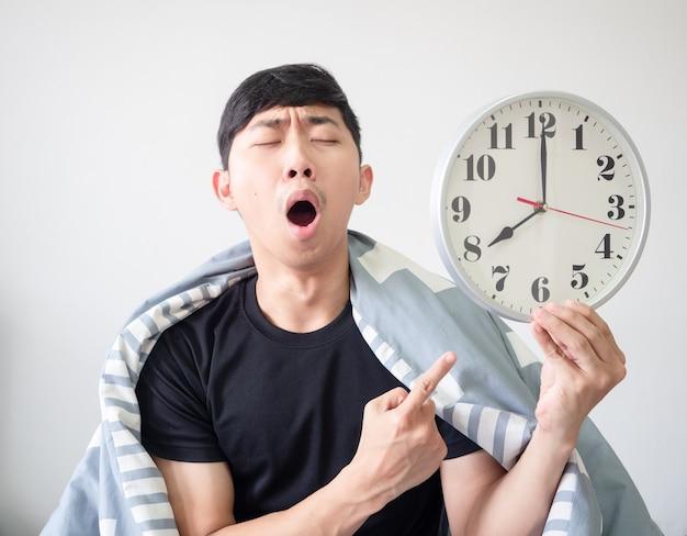 L'homme se réveille avec le corps de la couverture se sent somnolent et bâille le doigt pointé sur l'horloge en main
