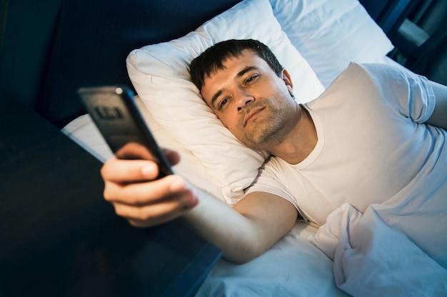 Un homme se réveille dans son lit et regarde le téléphone, éteint l'alarme et regarde l'heure, surfe sur internet, lit des messages, vérifie les réseaux sociaux.