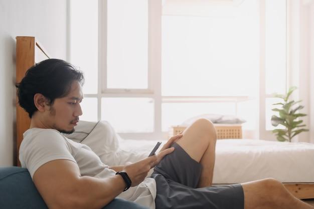 L'homme se sent détendu et utilise un smartphone dans son appartement