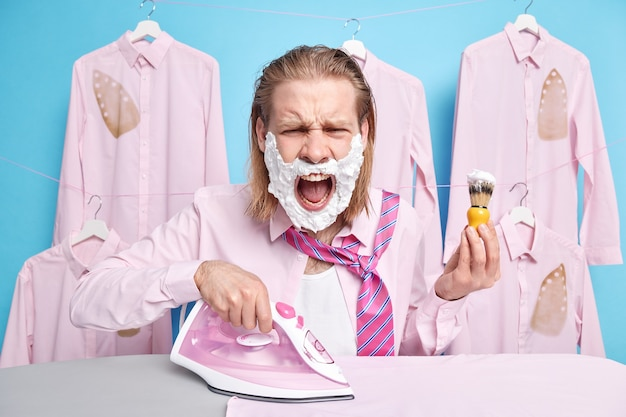 L'homme se sent fatigué de faire le ménage crie avec colère contre quelqu'un garde la bouche grande ouverte tient une brosse à raser des fers à repasser des vêtements sur une planche à repasser se réveille des poses tardives sur le bleu