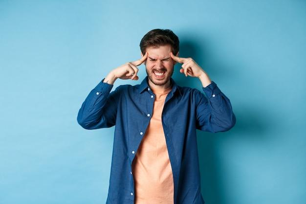 Homme se sentant malade, touchant la tête et grimaçant de migraine douloureuse, ayant mal à la tête ou se sentant étourdi, debout sur fond bleu.