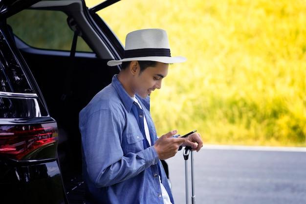 L'homme se tenait dans la voiture avec son téléphone portable et ses bagages