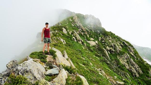 L'homme se tient au sommet de la montagne achisho et touche les nuages, sotchi, russie