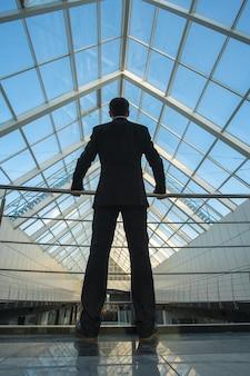 L'homme se tient sur le balcon du bureau
