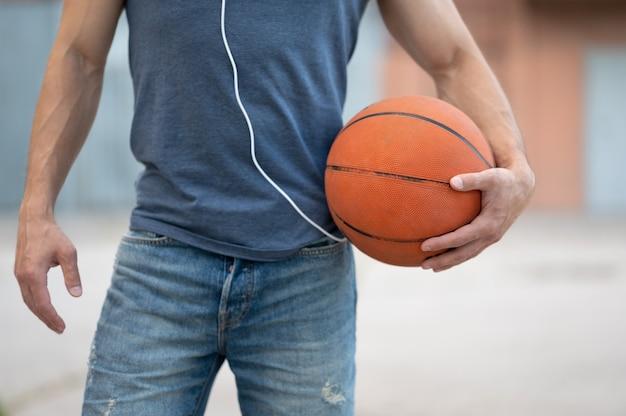 Un homme se tient avec un ballon de basket dans la rue en gros plan